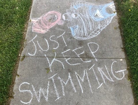 Chalk drawing that says Just Keep Swimming