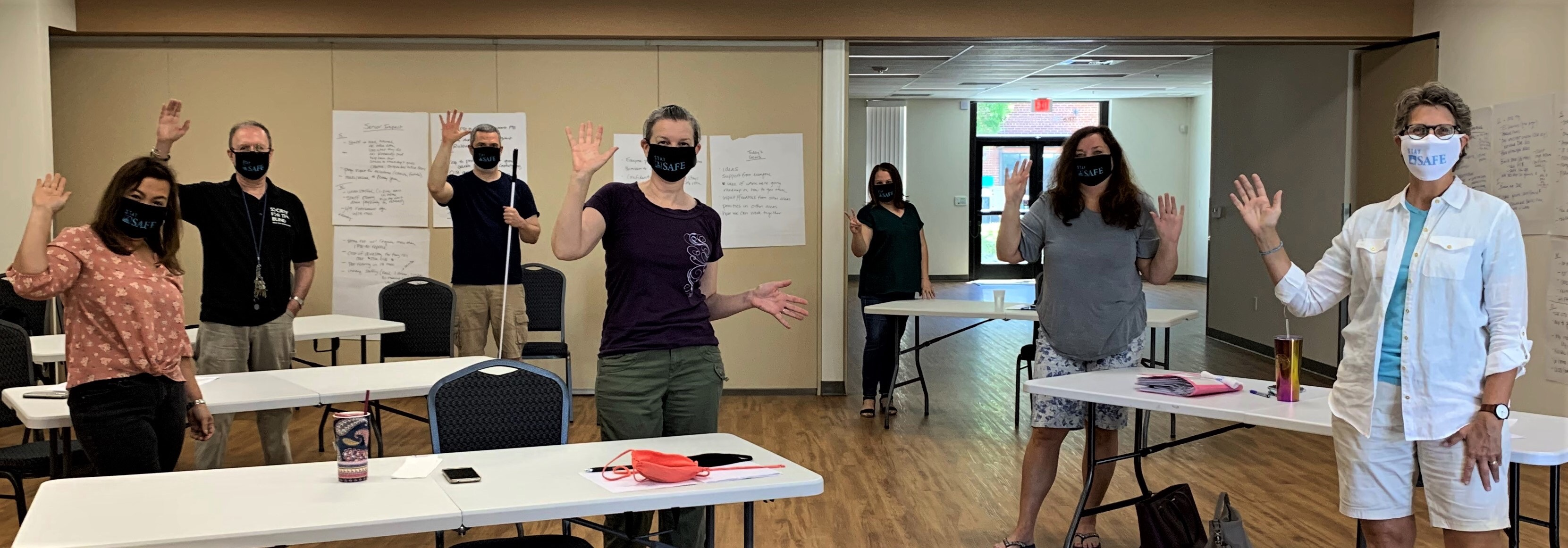 Members of the Society for the Blind pose wearing their Stay SAFE masks at a planning meeting
