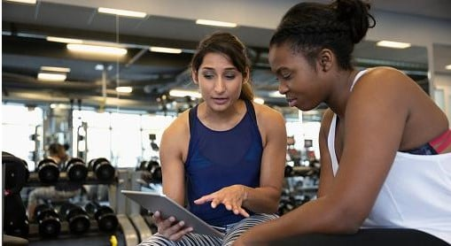 Women looking at tablet at a gym